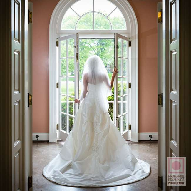 Bride poses by French glass doors