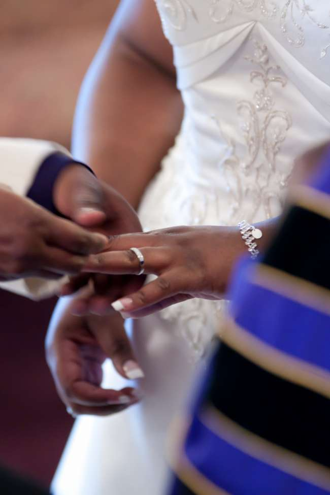 Groom Puts Ring on His Bride
