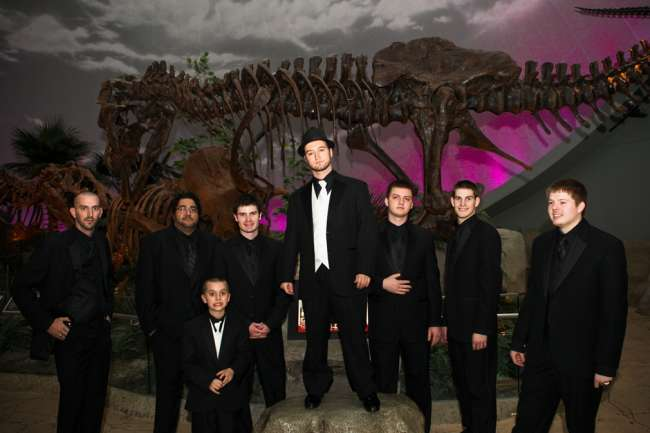 Groomsmen posing with dinosaur