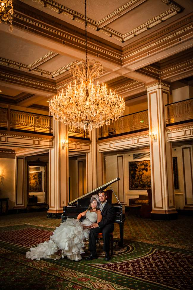 Bride & Groom Sitting at a Piano Under a Chandelier