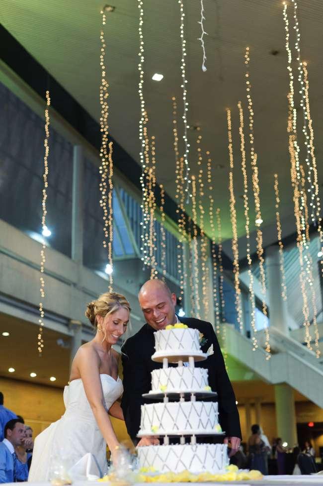 Bride & Groom Cutting Cake in Front of Elegant String Lights