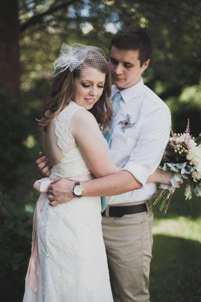 Groom With Pinwheel Boutonniere Embraces His Bride
