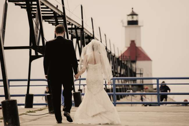 Bride & Groom Walking Down a Pier Towards a Lighthouse