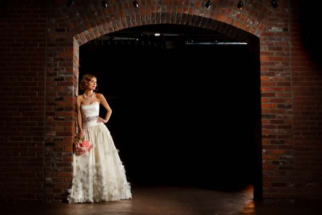 Bride Holding a Bouquet in Front of a Brick Wall