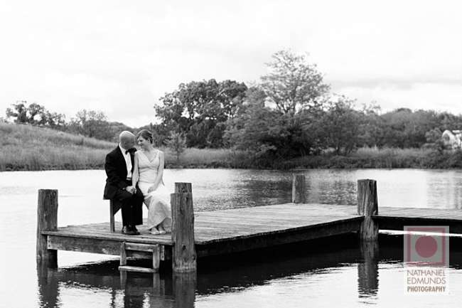 Bride and groom on lakeside dock