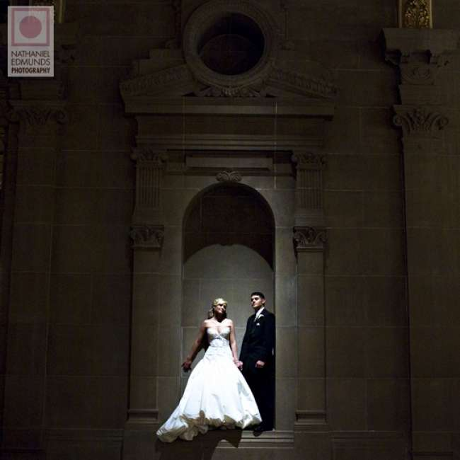 Bride and groom pose in historic building