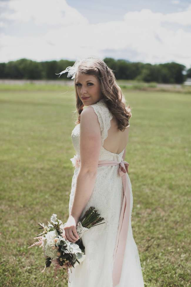 Bride Looking Over Her Shoulder in Open Field