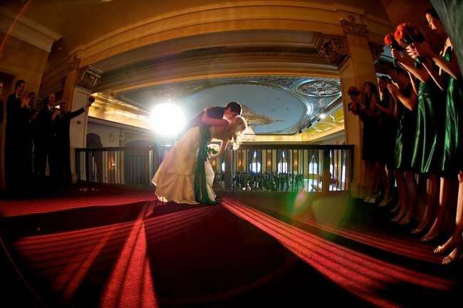 Wedding kis on balcony overlooking ballroom