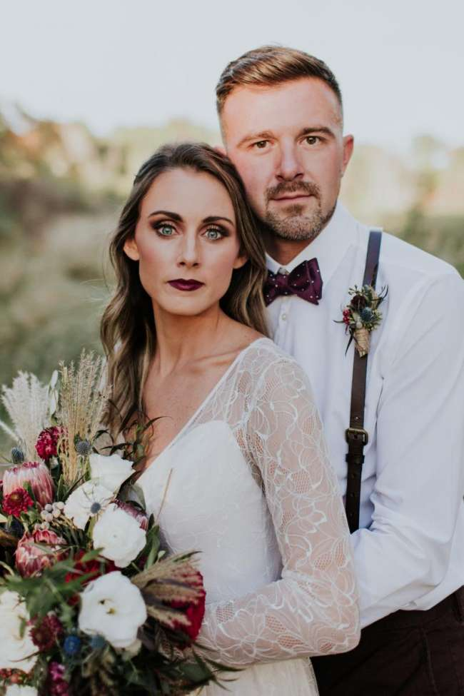 elopement  adventure burgundy groom style suspenders thistles protea long sleeve gown makeup